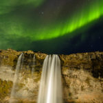 Aurora borealis or northern lights over Seljalandsfoss waterfall on the south coast of Iceland