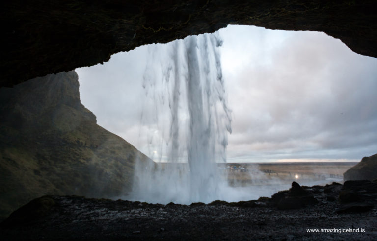 Enjoying view behind Seljalandsfoss waterfall on south coast of Iceland