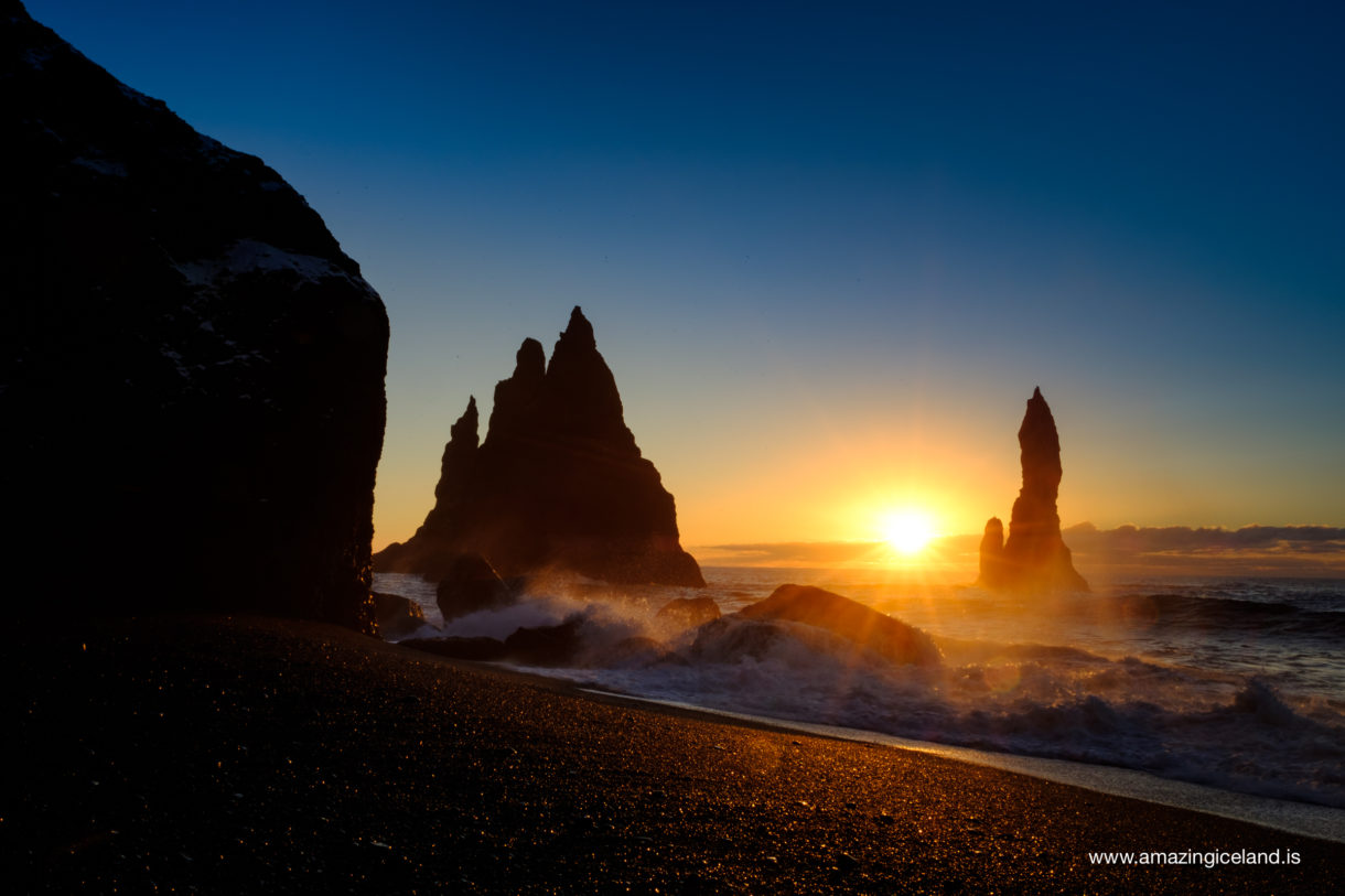 Reynisdrangar basalt columns at sunset on black sand beach in Iceland