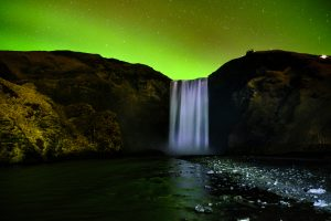 Northern lights over Skogafoss waterfall on south coast of Iceland