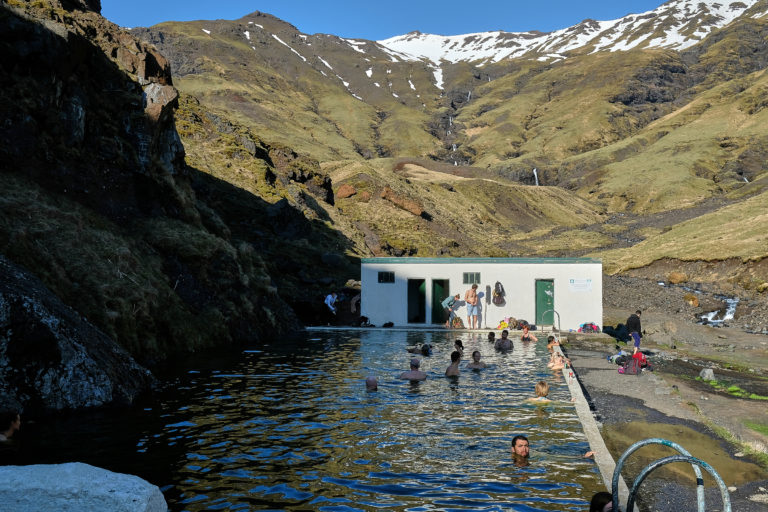 People enjoying geothermal natural pool Seljavallalaug on south coast of Iceland